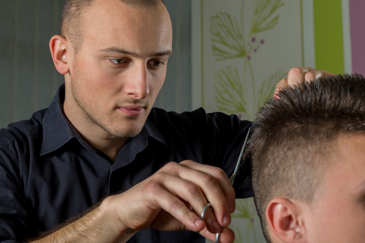 men's hair cutting with scissors in a beauty salon ...